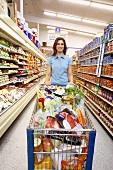 Woman pushing full shopping trolley through supermarket (USA)