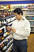 Man reading a wine bottle label in a supermarket