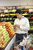 Man choosing apples from supermarket fruit stand