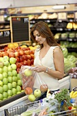 Woman putting apples into bag at supermarket fruit counter
