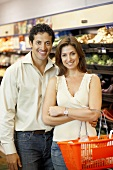 Smiling couple in a supermarket, woman holding basket