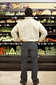 Man standing thoughtfully in supermarket vegetable section