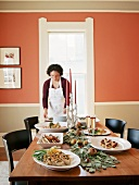 Köchin stellt Teller auf Buffetttisch im Wohnzimmer