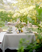 Laid table in the open air with hydrangeas and candles
