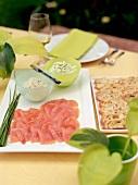 Räucherlachs, Aufstriche und Brot auf Tisch im Freien