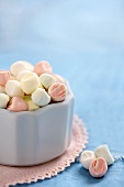Pastel-coloured mint sweets in and beside white bowl