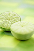 Two frozen lime halves on green background
