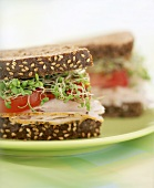 Turkey, tomato and sprout sandwich, halved