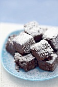 Small brownies with icing sugar on blue plate