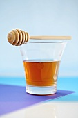 Glass of honey with honey dipper