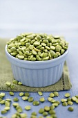 Green split peas in blue bowl on fabric napkin