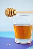 Honey dripping from honey dipper on glass of honey