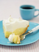 Piece of lemon meringue pie in front of blue coffee cup (USA)