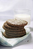 A pile of chocolate biscuits in front of a glass of milk