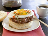 English muffin with burger and fried egg, coffee (USA)
