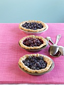 Three berry tarts in a row, spoons beside them (USA)