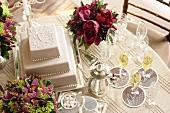 Three-tiered white wedding cake, flowers & champagne glasses