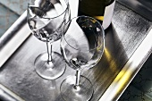 Two empty wine glasses and wine bottle on tray