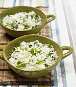 Two bowls of jasmine rice with coriander leaves