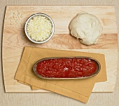 Pizza ingredients on board (dough, tomato sauce, cheese)