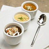 Three different soups in small bowls