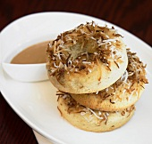 Three doughnuts with grated coconut, sauce in small bowl