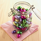 Coloured chocolate Easter eggs in a storage jar