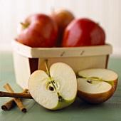 Äpfel im Spankorb, davor zwei Apfelhälften und Zimtstangen