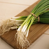 Two bunches of spring onions on chopping board
