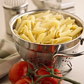 Cooked penne in strainer (steaming), fresh tomatoes beside it