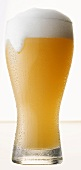 Glass of Wheat Beer Spilling Over, White Background