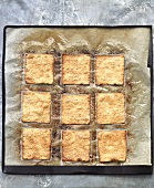 Caramelised pastry squares on baking parchment