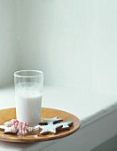 A glass of milk with assorted Christmas biscuits