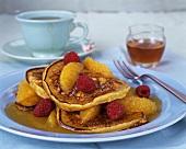 Pancakes with honey, orange segments and raspberries