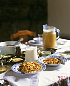 Breakfast table with cornflakes, milk and fruit juice