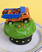 Toy wagon full of sweets on cup-cake with green cream
