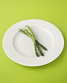 Three spears of green asparagus on white plate