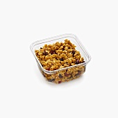 Small Container of Granola with Dried Fruit on a White Background