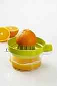 Orange Half on a Juicer, Freshly Squeezed Orange Juice in Juicer Pitcher