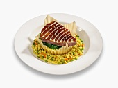 Tuna Steak in a Puff Pastry Shell on a Bed of Rice on White Plate, White Background
