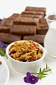 Small Bowl of Granola with Dried Fruit, Pitcher of Milk and Cookie Bars