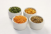 Four Small Bowls Full of Split Peas and Lentils, White Background