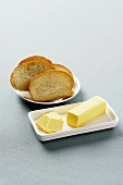 Partially Sliced Stick of Butter on a White Butter Dish with a Plate of Sliced Bread