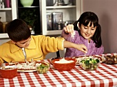 Boy and Girl Sitting at a Table Making Individual Pizzas, Toppings, Cheese and Broccoli