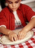 Young Boy Forming Pizza Dough onto a Pizza Pan with His Hands
