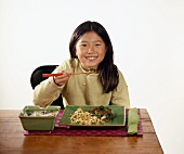 Child Sitting at Table Eating Broccoli Stir Fry and Fried Rice With Chopsticks, Bowl of Soup