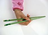 Childs Hand Holding Two Green Chopsticks