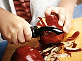 Childs Hands Peeling Red Delicious Apples with a Peeler on a Cutting Board