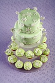 Two Tier Cake with Green Frosting and Snowflake Decorations on Two Tiers of Snowflake Cupcakes