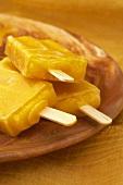 Three Mango Popsicles on a Dish